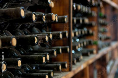dusty wine bottles on a wooden shelf in a wine cellar Wallpaper Mural