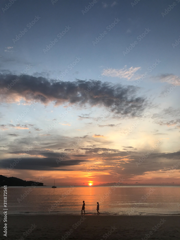 man and woman are waliking into the scene of golden sunset light with amazing twilight sky and yacht in clear sea