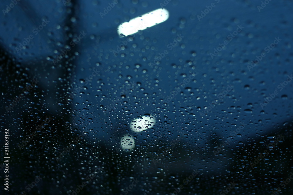 Fototapeta water rain drop on glass window with blur street light in night town background