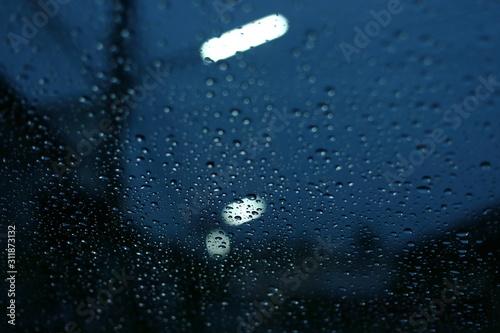 Obraz water rain drop on glass window with blur street light in night town background - fototapety do salonu