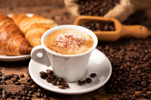 Fotografia A cup of cappuccino with coffee bean as background.