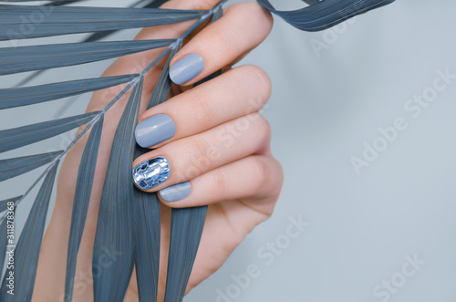 Beautiful female hand with blue nail design Fototapeta