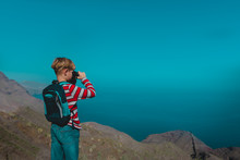 Boy Looking Through Binocular On Travel In Mountains Near Sea