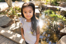 Portrait Of A Cute Young Girl Standing Near A Pond In The Park