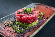 Gourmet Fish Tartar Raw From Tuna Fillet With Hashed Avocado, Wasabi And Japanese Spice As Closeup On Modern Design Plate