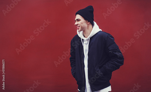 Fotografia fashion man in black hat dressed casual on red wall background