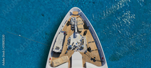 Aerial drone ultra wide photo of luxury yacht with wooden deck docked in tropical exotic destination