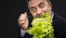 Man Holding And Eating Lettuce