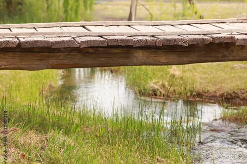 puente sobre arroyo con agua y fondo de árboles verdes Canvas Print