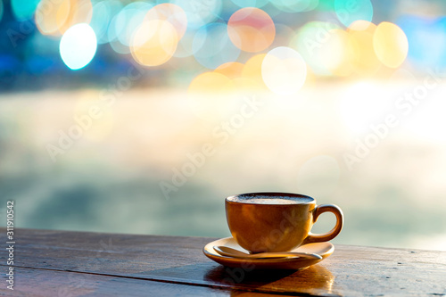 Fotografía  Hot coffee cup on wooden table with warm sunlight and the misty at lake in morni