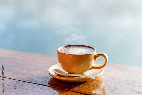 Fototapeta Hot coffee cup on wooden table with warm sunlight and the misty at lake in morning against blurred Chinese village in Mae Hong Son, Thailand obraz