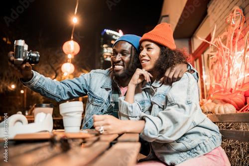 Fototapeta Happy lovely couple making photo in street cafe obraz na płótnie