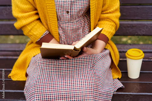Fotografía  A woman is sitting on a park bench and holding a book and bamboo cup with hot coffee