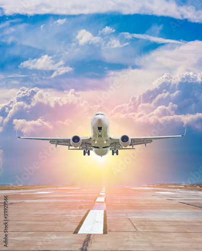 White passenger aircraft take off from airport runway against the backdrop of a scenic evening sky with sun rays Fototapete