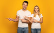 In the same direction. A beautiful couple is posing on a yellow background, wearing white t-shirts, pointing to the left with their hands and smiling at the camera.