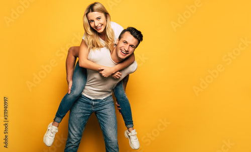 Obraz Playing around. Full-length photo of a happy man, giving his smiley girlfriend a piggyback ride while laughing out of joy. - fototapety do salonu