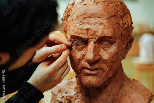 Obraz Close up of sculptor finishing an clay head eye - fototapety do salonu