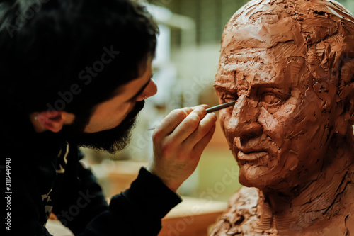 Obraz Focused sculptor finishing a clay head - fototapety do salonu