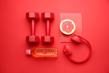 Dumbbells With Notebook, Headphones Grapefruit And Bottle Of Water On Color Background