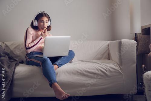 Teenage girl with laptop eating popcorn while watching movie late in evening Tapéta, Fotótapéta