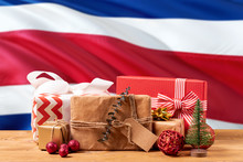 Costa Rica New Year Celebration Theme. Wrapped Christmas Gifts On Waving National Flag Background. Merry Christmas Concept.
