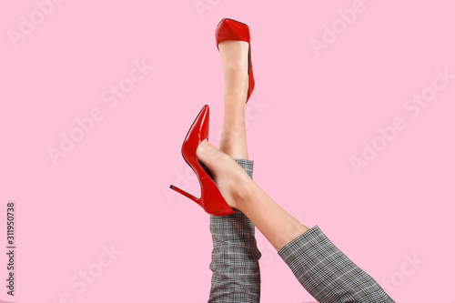Legs of young woman in high-heeled shoes on color background Obraz na płótnie