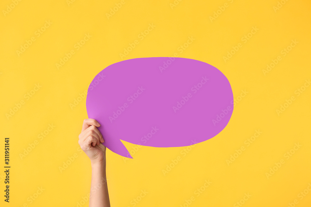 Fototapeta Female hand with blank speech bubble on color background