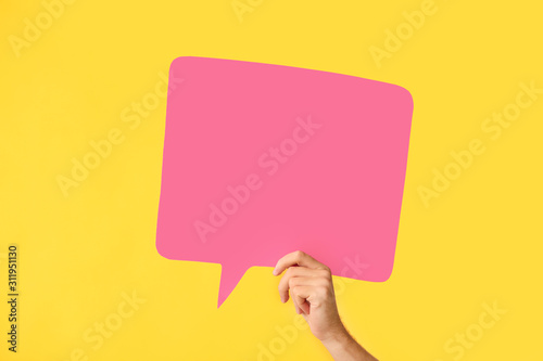 Fototapeta Female hand with blank speech bubble on color background obraz