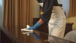 Housemaid in gloves wipe the table with rag in hotel room