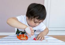 Preschool Kid Putting Glue Sti...