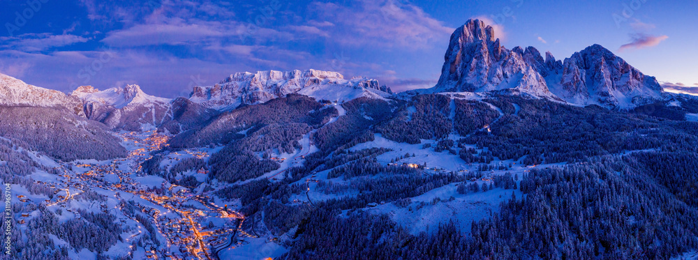 Fototapeta Beautiful panoramic view of Dolomites mountains at dusk during winter time. Magical winter mountain purple sunset with a mountain ski resort village. Christmas time.