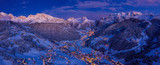 Fototapeta Na ścianę - Beautiful panoramic view of Dolomites mountains at dusk during winter time. Magical winter mountain purple sunset with a mountain ski resort village. Christmas time.
