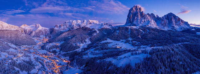 Beautiful panoramic view of Dolomites mountains at dusk during winter time. Magical winter mountain purple sunset with a mountain ski resort village. Christmas time.