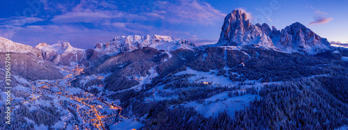Beautiful panoramic view of Dolomites mountains at dusk during winter time. Magical winter mountain purple sunset with a mountain ski resort village. Christmas time. - 311965704