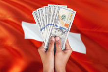 Switzerland Financial Concept. Female Hand Holding Dollar Banknotes On National Flag Background. Currency And Money Theme With Copy Space.
