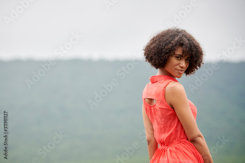 Gorgeous biracial young woman poses looking back over her shoulder in red dress Canvas Print
