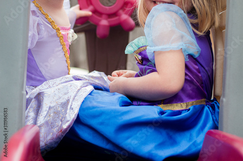 Obraz na płótnie young girls in princesss dresses play together on toy