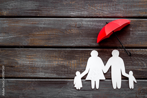 Fototapeta Live insurance concept. Family silhouette protected by umbrella on dark wooden background top-down copy space obraz