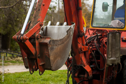 Worker driving a vintage backhoe loader (bulldozer, bull dozer,excavator) with hydraulic bucket Canvas Print