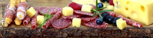 Photo Meat and cheese plate antipasti snack with Prosciutto ham, Parmesan, Blue cheese, Cantaloupe melon and Olives on olive wood serving board