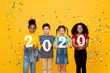 canvas print picture - Cute smiling mixed race children showing numbers 2020 celebrating new year