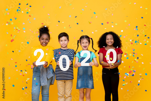 Cute smiling mixed race children showing numbers 2020 celebrating new year - 311995580