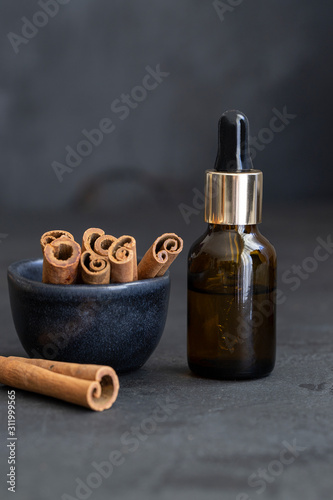 Photo Essential cinnamon oil in glass bottles and cinnamon natural sticks