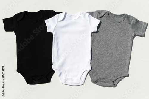 Obraz A set of three blank baby bodysuits on a cream textile background in harsh light - Black, white and grey baby grow set mockup -  Styled stock photography - fototapety do salonu