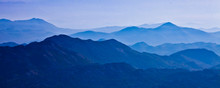 With Blue Misty Mysterious Mountains In The Distance And An Orange Pastel Sky. Distant Blue Mountains.