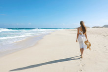Young Woman Walking On Empty Wild Beach With White Sand And Blue Sky In Corralejo, Canary Islands