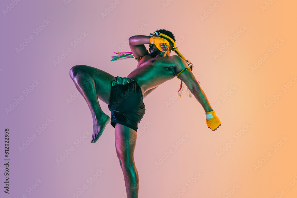 Fototapeta Muay thai. Young man exercising thai boxing on gradient background in neon light. Fighter practicing, training in martial arts in action, motion. Healthy lifestyle, sport, asian culture concept.