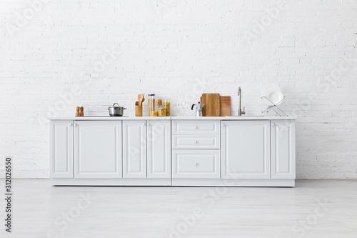 Fotografia, Obraz minimalistic modern white kitchen interior with kitchenware near brick wall