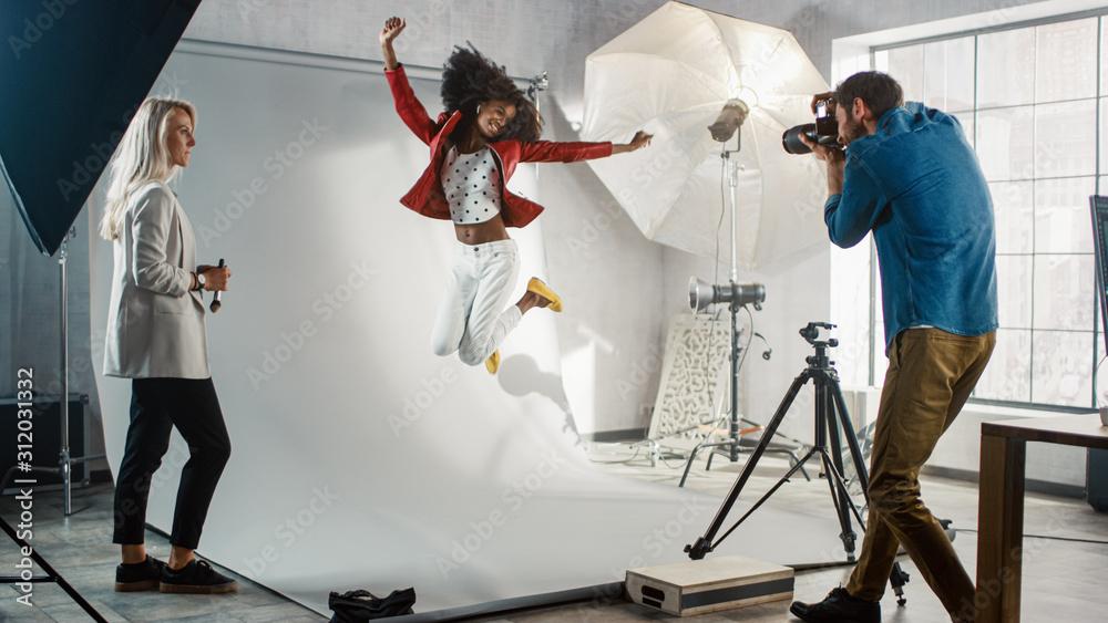 Fototapeta Backstage of the Photo Shoot: Moment Photographer Taking Photos of Jumping Beautiful Black Model with Professional Camera. Fashion Magazine Studio Photoshoot