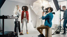 Cameraman Filming Make-up Artist Applies Makeup To A Beautiful Black Model. They Pose For A Video Clip. Stylish Fashion Magazine. Photo Shoot Done With Pro Equipment In A Studio